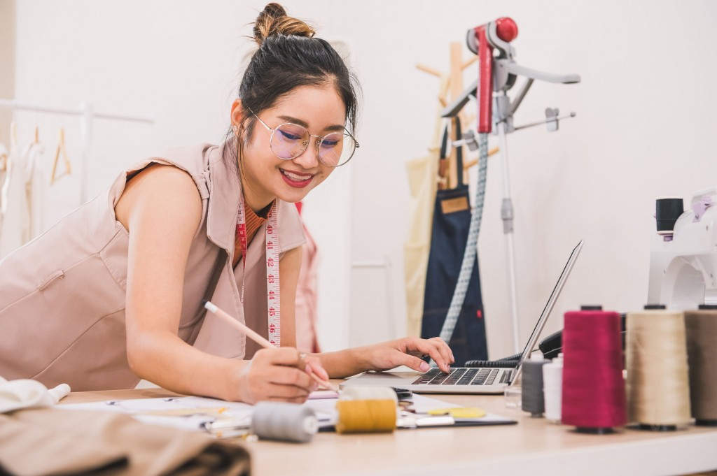 Attractive Asian Female Fashion Designer Working In Home Office