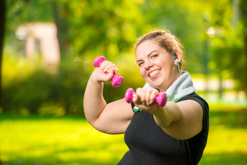 Portrait Of Smiling Plus Size Woman With Dumbbells In The Park D