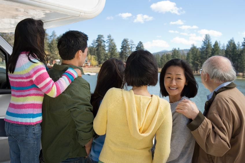 Three Generation Family Looking At Lake Back View