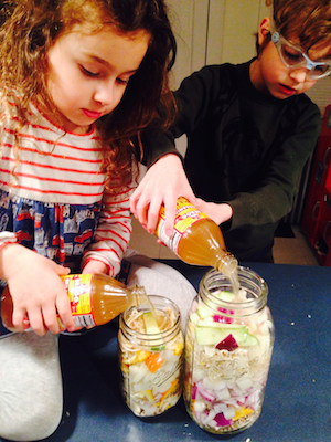 Colby and Ayla Bruntil filling their Fire Cider jars.
