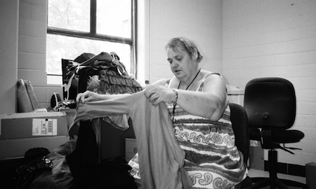 Lois Howard sorts donated clothing at the offices of Safe Harbor, an emergency shelter in Ashland, Kentucky. Photo by Laura Michele Diener.